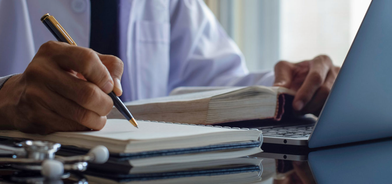 doctor takes notes on legal pad while consulting book and computer
